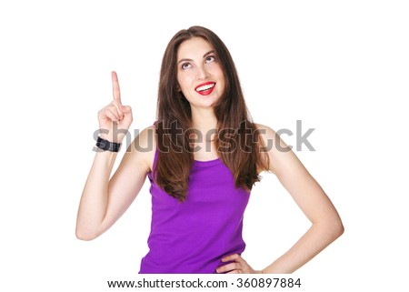 Woman in purple tank top pointing showing and looking up - Isolated on white background. Beautiful young Caucasian  female model in studio. - stock photo