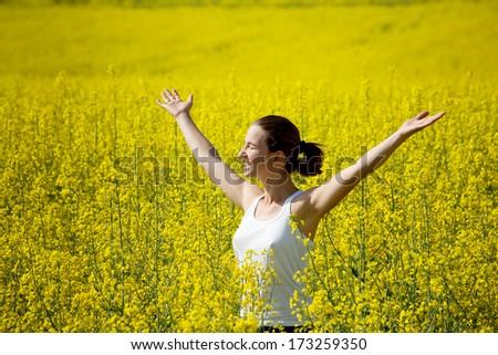 Woman in rapeseed field - stock photo