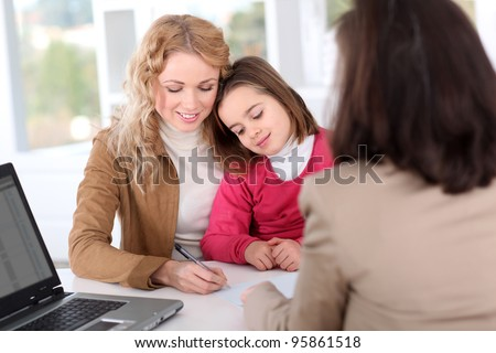 Woman in real-estate agency with kid - stock photo