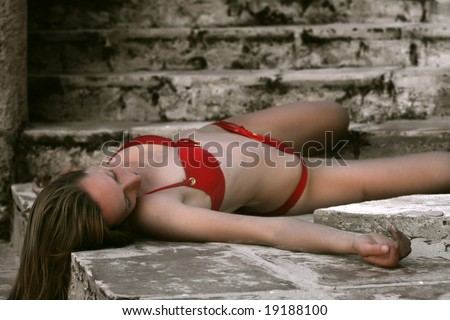 woman in red bikini dead on the stairs - stock photo