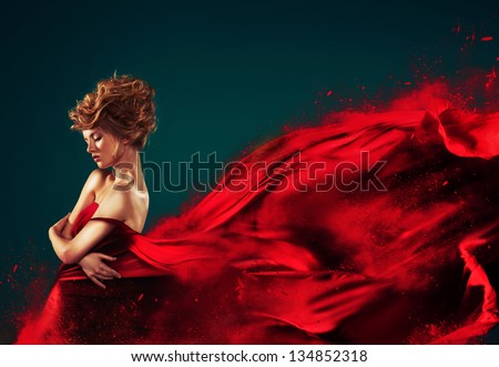 Woman in red blowing flying red dress dissolving in splash - stock photo