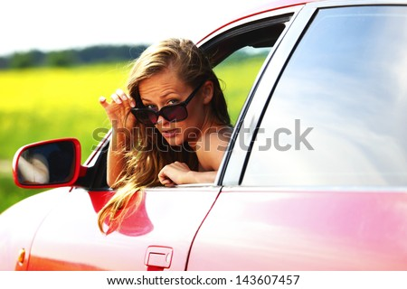 woman in red car get out window