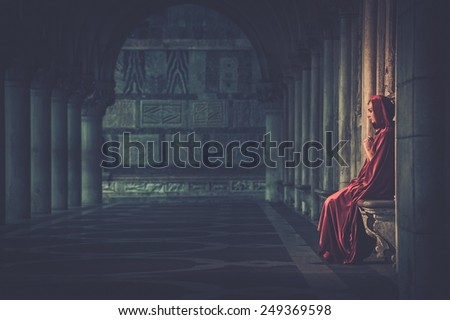 Woman in red cloak praying alone - stock photo