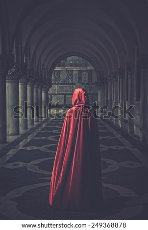 Woman in red cloak walking away - stock photo