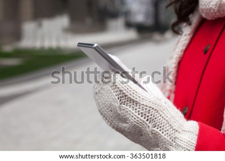 Woman in red coat hold smartphone in wool gloves - stock photo