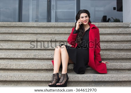 woman in red coat talking on the cellphone sitting in stairs