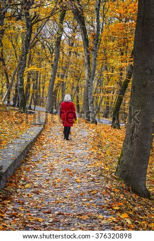 Woman in red coat walking up the path in autumn park.