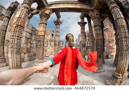 Woman in red costume with scarf leading man by hand to Qutub Minar tower in Delhi, India