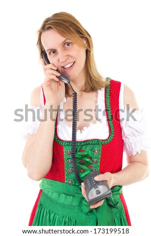 Woman in red dirndl dialing a friend - stock photo