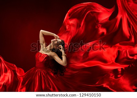 Woman in red dress blowing with flying fabric, fashion girl posing over silk fluttering cloth
