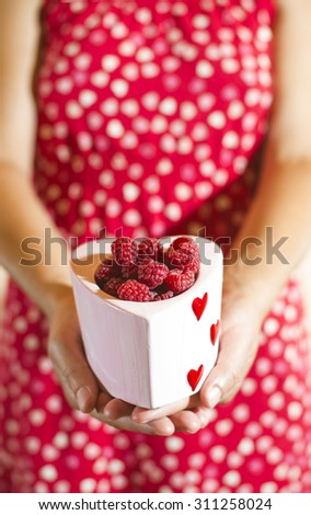 Woman in red dress holding a cup of raspberries