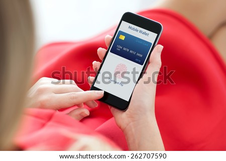 woman in red dress holding a phone with app mobile wallet and fingerprint for online shopping - stock photo