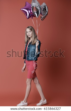 Woman in red dress holding balloons on the red background