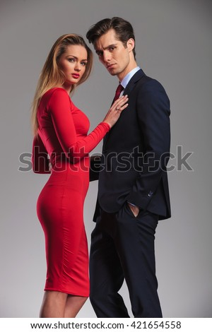 woman in red dress holding hand on husband's chest and looks at the camera - stock photo