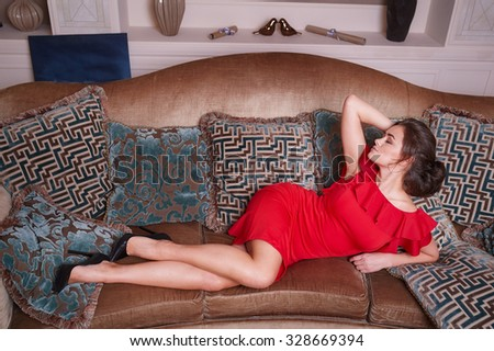 woman in red dress lying on the sofa in the living room. - stock photo