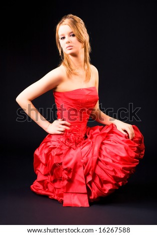 Woman in red dress. On dark background. - stock photo