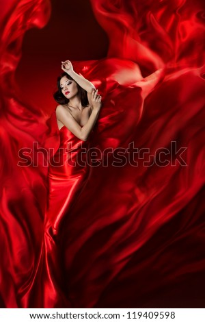 Woman in red dress posing with waving fabric, Girl fantasy dreams concept - stock photo