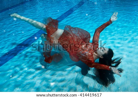 Woman in red dress underwater lying on the bottom of the pool.