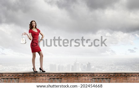 Woman in red dress with bag in hand