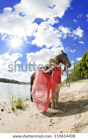 Woman in red dress with bright makeup on the horse outdoors