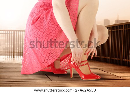 woman in red dress wooden floor of terrace and sunset  - stock photo