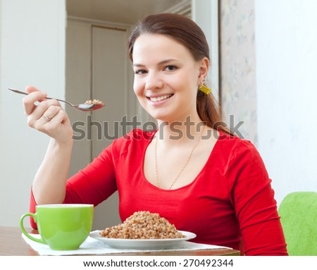woman in red eats buckwheat porridge with spoon at home - stock photo