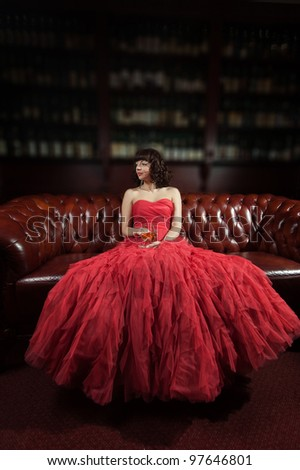 Woman in red evening dress sitting on the sofa - stock photo