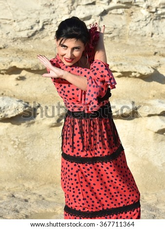 Woman in red flamenco dress. Portrait of Flamenco dancer in yellow rock background. Photo of flamenco dancer. Beautiful brunette woman,flamenco dancer in natural background.Dancing woman.Spanish woman - stock photo