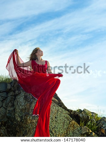 Woman in red flying dress on rock in summer - stock photo