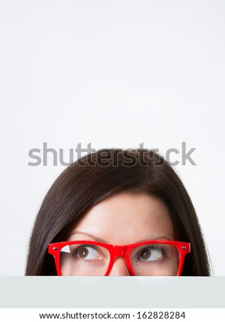 Woman in red-framed eyeglasses looking away, close-up shot