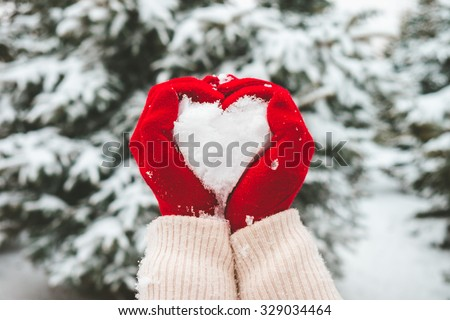 Woman in red gloves holds snow in hands in shape of heart. - stock photo