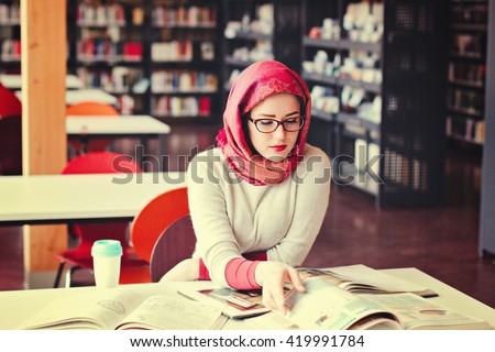 Woman in red headscarf working looking into the book - stock photo