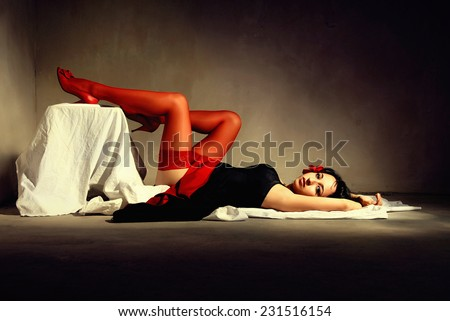 Woman in red hose on the floor - stock photo