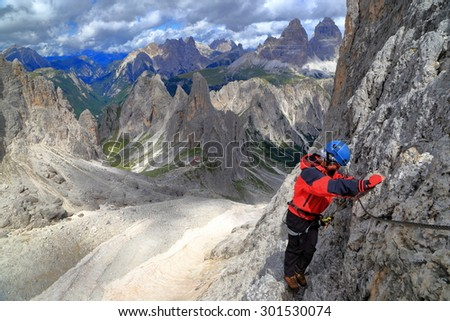 "Woman in red jacket climbs via ferrata ""Merlone"", Cadini di Misurina, Dolomite Alps, Italy - stock photo"