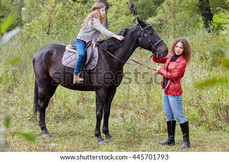 Woman in red jacket holds by the bridle horse on whom her daughter sits.