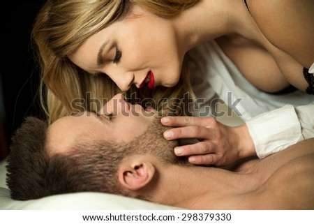 Woman in red lips kissing her lover - stock photo
