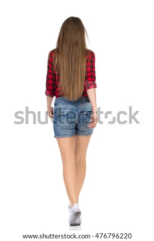 Woman in red lumberjack shirt, jeans shorts and white sneakers walking away. Rear view. Full length studio shot isolated on white.