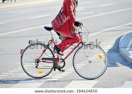 Woman in red. On bike. - stock photo