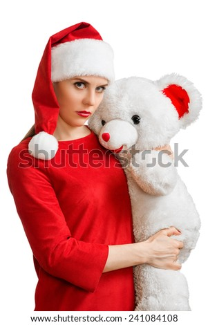 Woman in red santa hat, frowning at camera, holding white toy bear