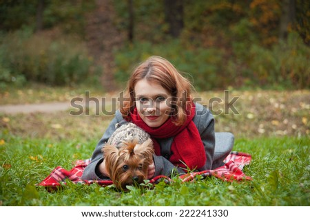 woman in red scarf holding a Yorkshire Terrier lying on the grass