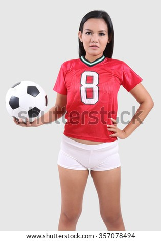 Woman in red shirt and white short holding football on her hand