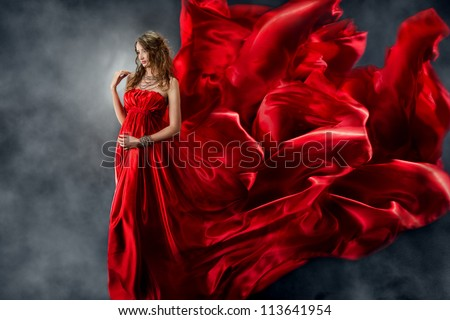 Woman in red silk dress waving on wind. Flying and fluttering gown cloth over gray background - stock photo