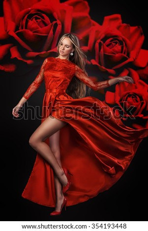 Woman in red waving dress dancing with flying fluttering fabric - stock photo