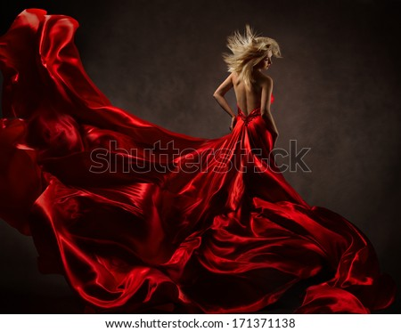 Woman in red waving dress with flying gown fabric. Back side view - stock photo