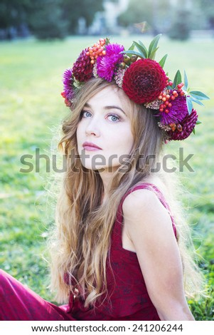 Woman in red with red flower wreath on a green meadow - stock photo