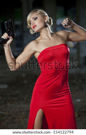 Woman in retro look playing a scene where she has been shot from a gun - stock photo
