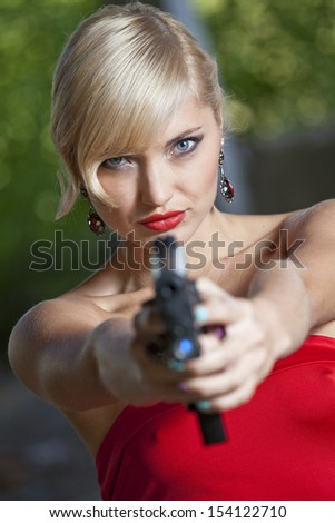 Woman in retro look pointing a gun at the camera - stock photo