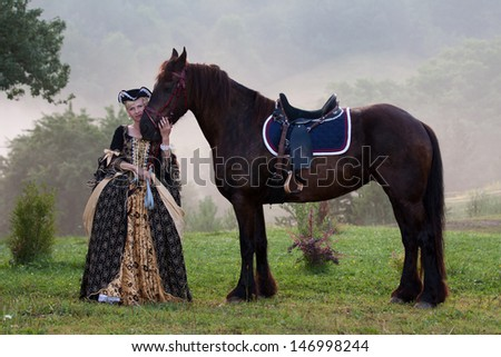 Woman in royal baroque dress, standing next to a horse in the fog - stock photo