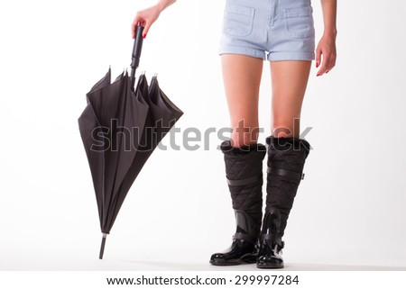 Woman in rubber boots and  black umbrella standing on a white background. - stock photo