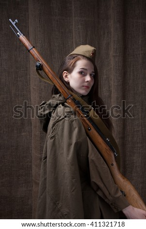Woman in Russian military uniform with rifle. Female soldier during the second world war. - stock photo